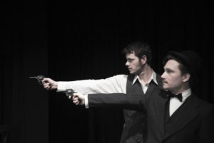 Photo of Joshua Waters as Holmes and Blake Selmes as Watson holding pistols ready to fire (Photo by Danny Scott)